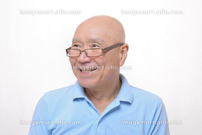 老眼鏡をかけた笑顔のシニアの販売画像
