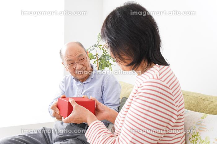プレゼントを渡す高齢の夫婦の販売画像