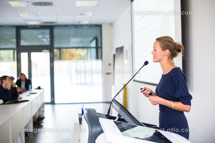 Pretty, young business woman giving a presentation in a conference/meeting setting (shallow DOF  color toned image)の販売画像
