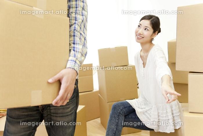 段ボールを運ぶ男性と指示する女性の販売画像