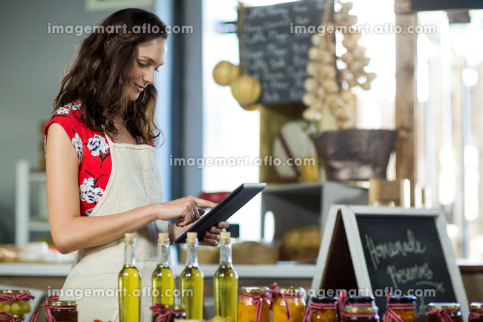 Female shop assistant using digital tablet at the counterの販売画像