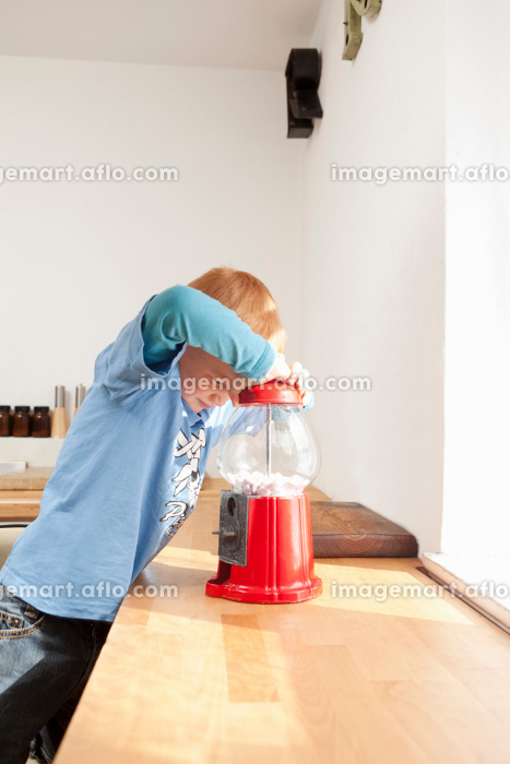 Boy opening gum ball machine in kitchenの販売画像