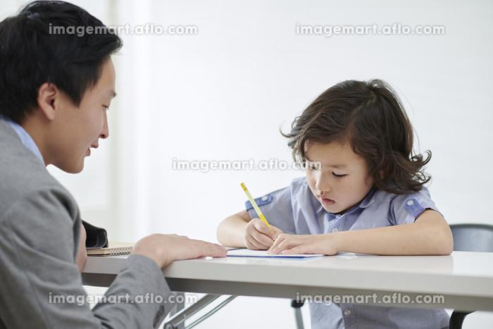 先生に勉強を教わる日本人の男の子