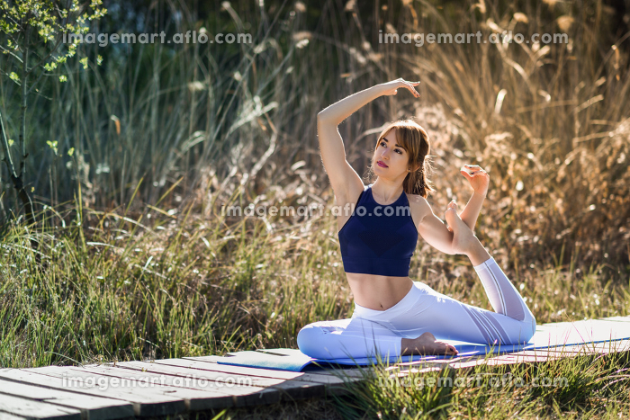 Young woman doing yoga in nature. Female wearing sport clothes in mermaid figure.の販売画像