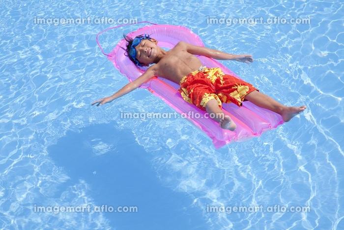 浮き輪でプールに浮かぶ水着姿の男の子の販売画像