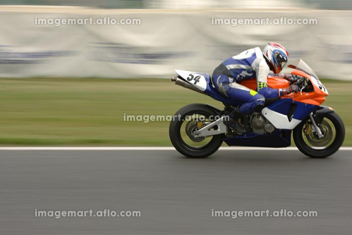 バイクに乗るレーサーの横向きの販売画像