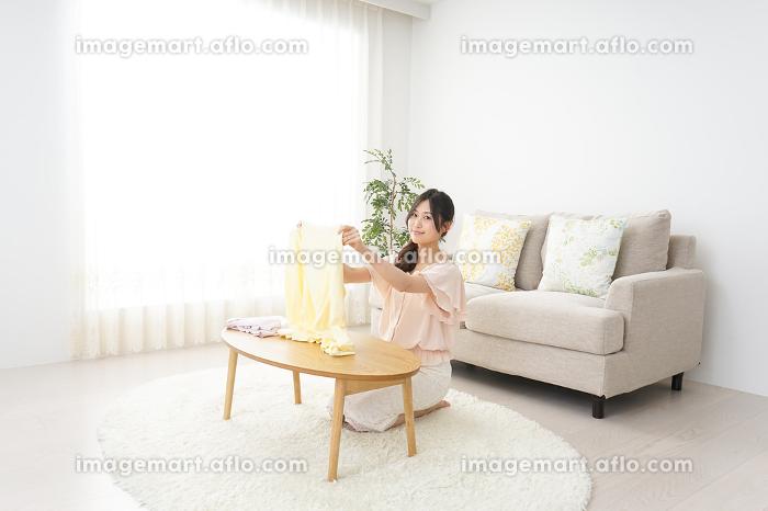 洗濯物をたたむ若い女性の販売画像