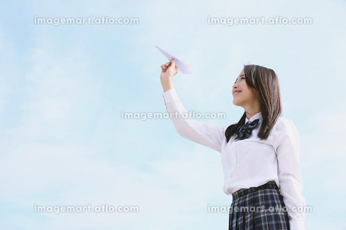 紙飛行機を飛ばす女子高生