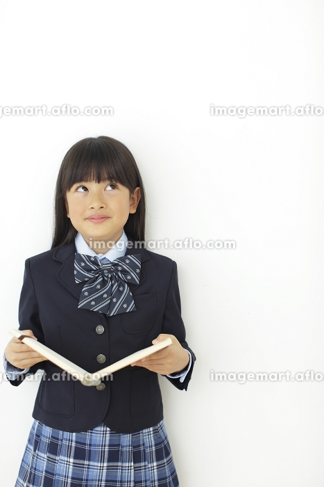 ノートをひらく制服姿の小学生の女の子の販売画像