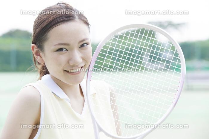 テニスラケットを持って微笑む女性の販売画像