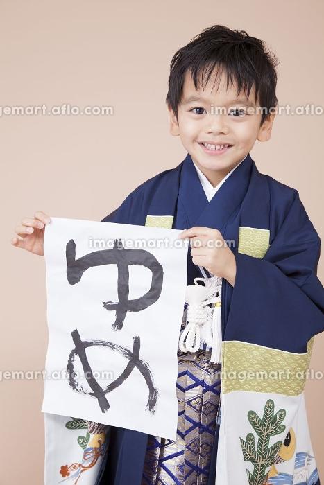 半紙を持って微笑む男児の販売画像