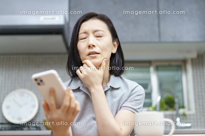 疲れた表情でスマートフォンを持つ女性の販売画像