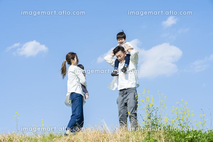 笑顔で散歩する親子4人の販売画像