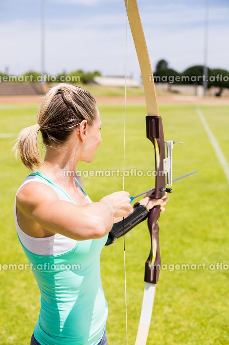 Happy female athlete practicing archeryの販売画像