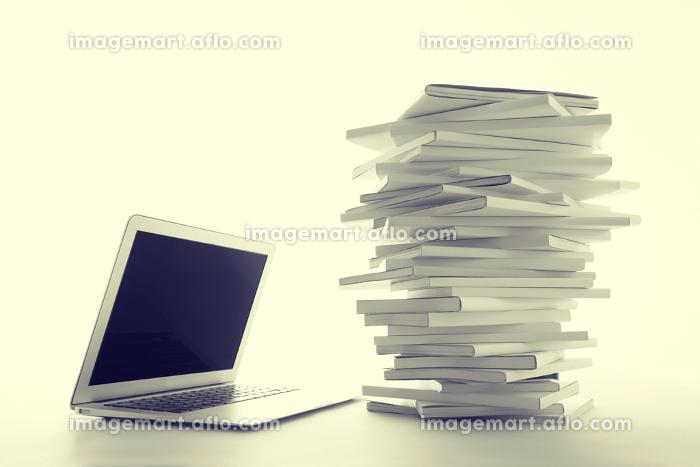 積み重ねた白い本とノートパソコンの販売画像