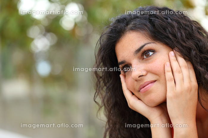 Woman dreaming looking away in a parkの販売画像