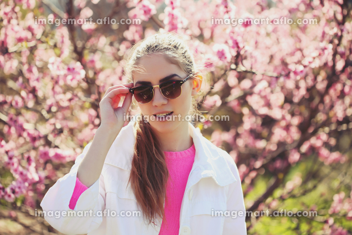 Fashion portrait of gorgeous young sexy blond girl posing in a lush garden in the spring in a stylish white jacket, a pink blouse and striped skirt and sunglasses. Bright young outfit.