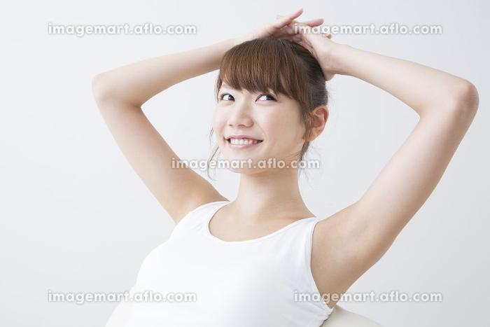 両手を頭の上に載せる女性の販売画像