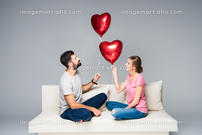 Couple sitting on couch with red balloonsの販売画像