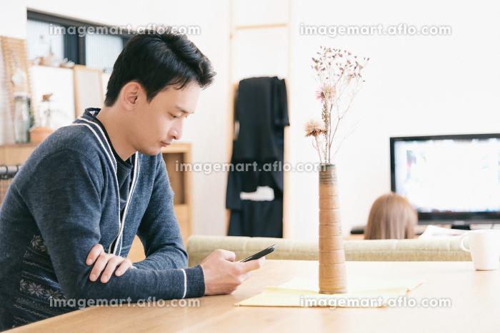 スマートフォンを見る男性の販売画像