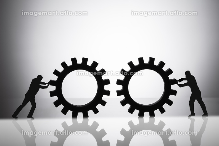 Silhouette Of Two Businesspeople Joining Gearsの販売画像