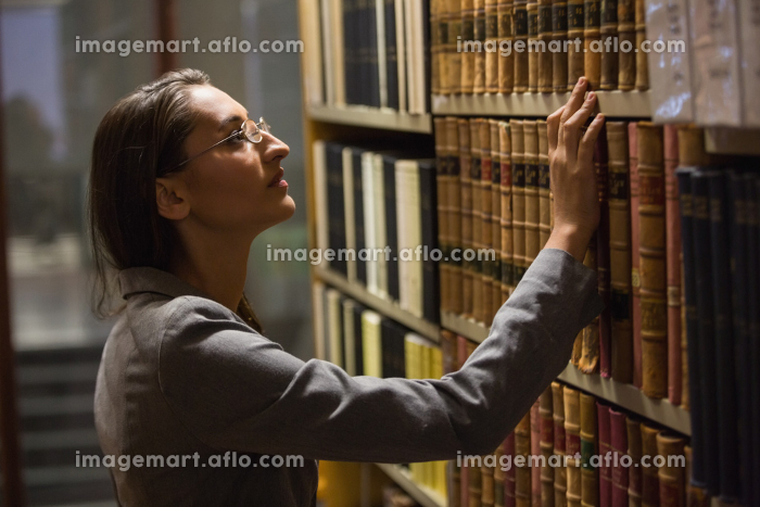 Lawyer picking book in the law libraryの販売画像