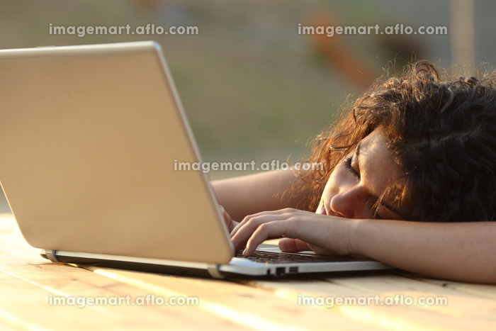 Overworked tired woman resting over a laptopの販売画像