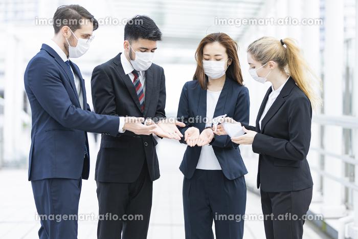 除菌スプレーを使うビジネスチームの販売画像