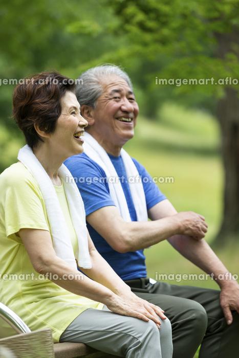 ベンチに座るシニア夫婦の販売画像