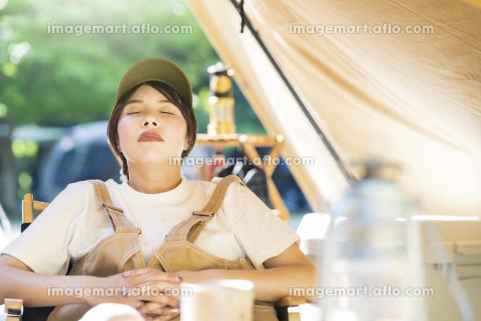 ソロキャンプイメージ・テントの前で昼寝する若い女性の販売画像