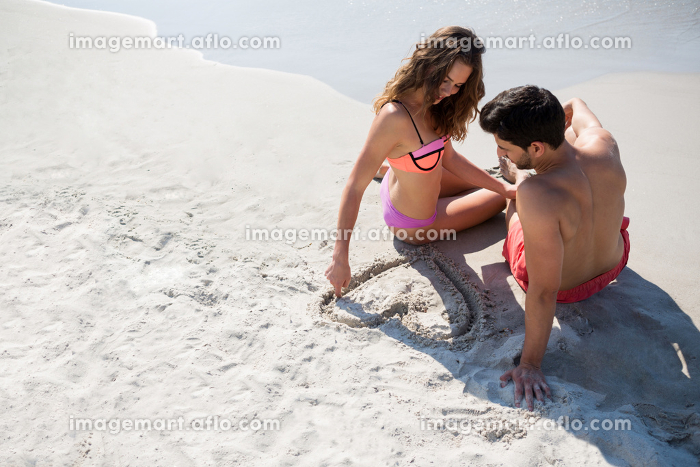 Young woman carving heart shape in sand while sitting with boyfriend at beachの販売画像