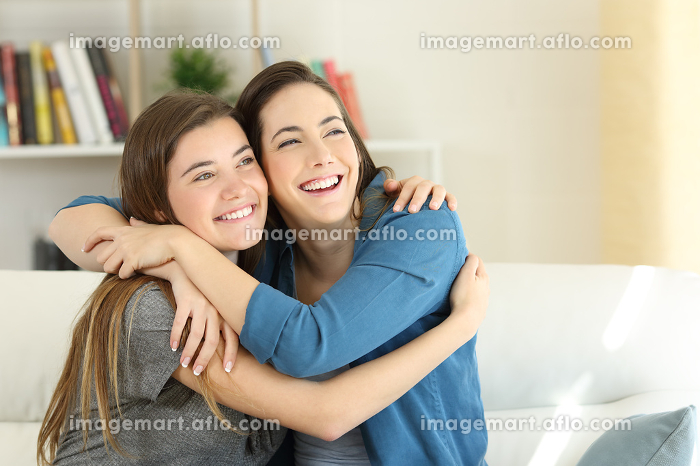 Two happy friends or sisters hugging at homeの販売画像