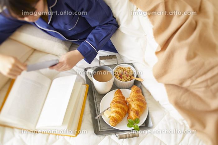 ベッドで朝食をとる日本人女性の販売画像