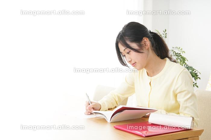 自宅で勉強をする若い女性の販売画像
