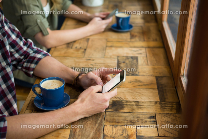 Man and woman using mobile phones in coffee shop