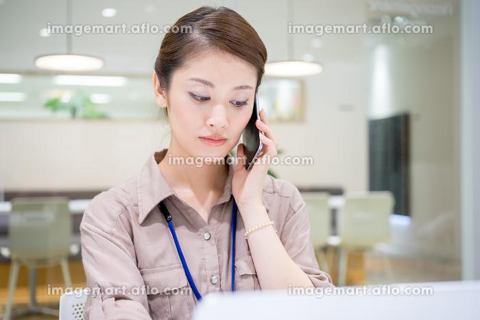 真剣な表情で仕事をする会社員(女性・電話・パソコン)の販売画像