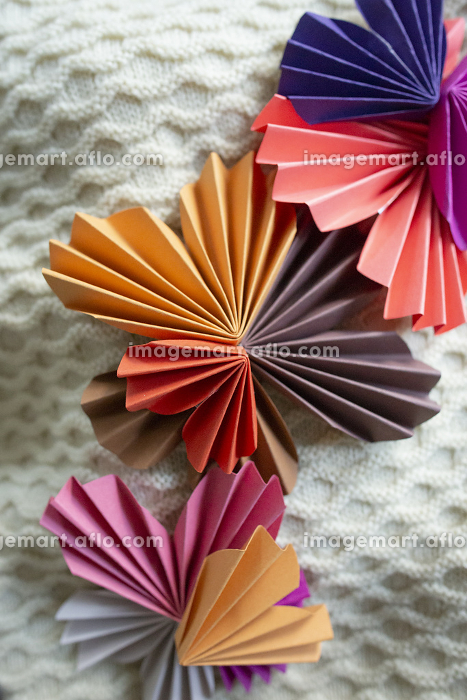 Multi-colored paper hearts arranged on textured knit backgroundの販売画像
