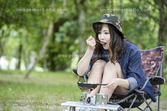 一人キャンプで料理をする若い日本人女性の販売画像