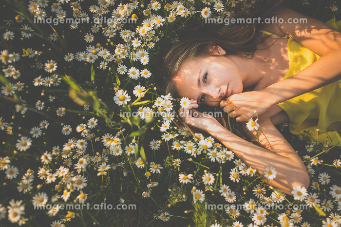 Portrait of young  woman with radiant clean skin lying down amid flowers on a lovely meadow on a spring/summer dayの販売画像