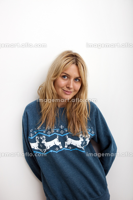 Portrait of smiling woman in sweater against white backgroundの販売画像