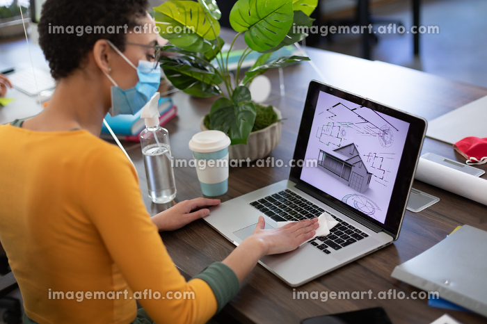 Mixed race woman wearing face mask disinfecting laptop in office. hygiene in workplace during coronavirus covid 19 pandemic.の販売画像