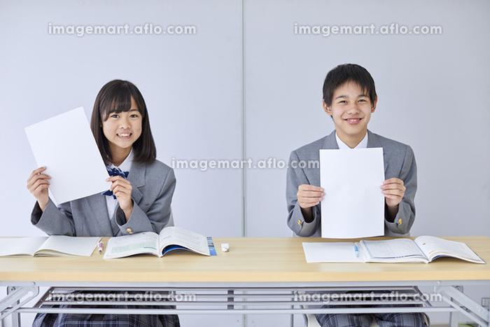 白紙の紙を持つ男女の中学生