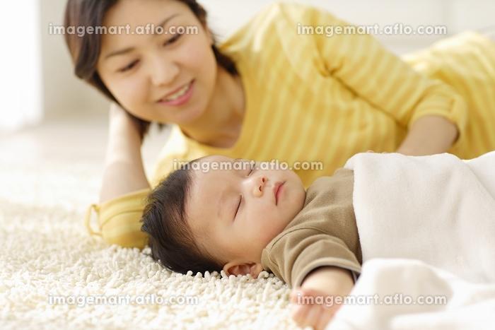 リビングで昼寝をする赤ちゃんと添い寝するお母さんの販売画像