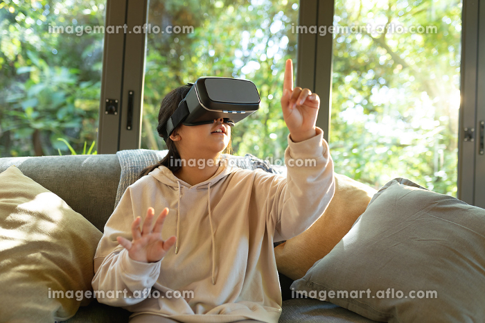 Smiling asian girl wearing vr headset touching with her finger sitting on sofa. at home in isolation during quarantine lockdown.の販売画像