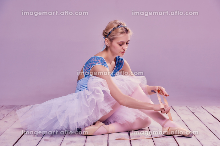 Professional ballerina putting on her ballet shoes.の販売画像