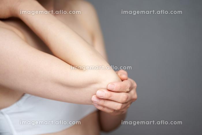肘のトラブルに悩む中年の日本人女性の販売画像