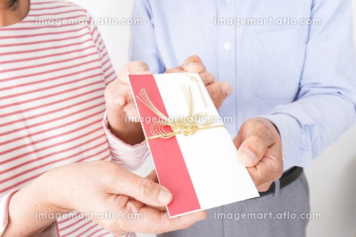 お祝いを渡すシニアの夫婦の販売画像