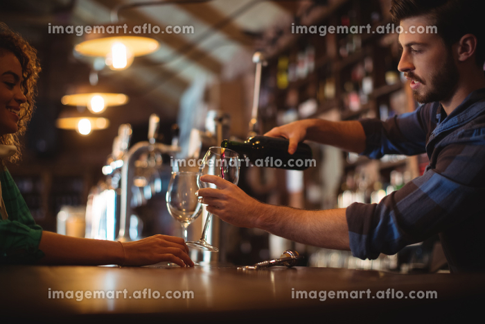 Male bar tender pouring wine in glassesの販売画像