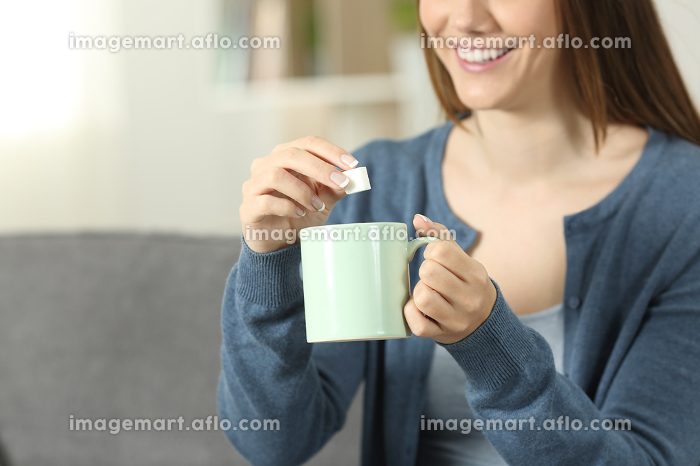 Smiley woman throwing sugar into coffee mug at homeの販売画像