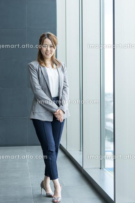 窓際に立つ社会人の女性(ビジネスイメージ)の販売画像